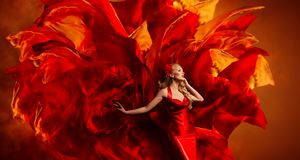 Woman Art Fantasy, Dancing Fashion Model on Red Fabric Color Explosion stock photo