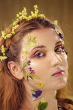 Woman with art fashion make up on face. Brown background. Girl with crative flower makeup on face royalty free stock photo