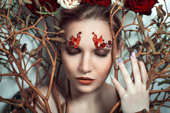 Woman with art make up. Beautiful young girl lady actress model character tree rose fairy tale. Bold creative look fashion style. Ideal expressive makeup bright Stock Photos