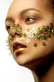 Woman with art make up with golden thumbtacks Royalty Free Stock Photography