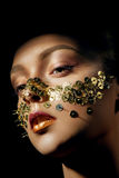 Woman with art make up with golden thumbtacks Stock Photography