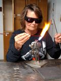 Flame Torch Artisan Working. Woman artist blowing glass royalty free stock photo