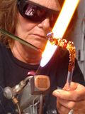 Flame Torch Artisan Working. Woman artist blowing glass stock image