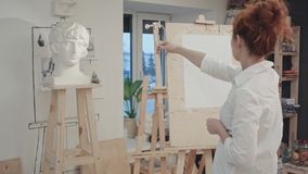 Woman artist drawing plaster bust in the workshop. Professional shot on BMCC RAW with high dynamic range. You can use it e.g. in your commercial video stock photos
