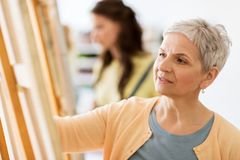 Woman artist with easel drawing at art school. Art school, creativity and people concept - happy senior women artist with easel drawing at studio royalty free stock photo