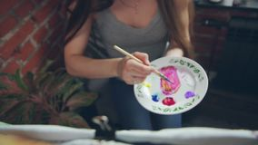 Woman-artist at easel paints on canvas. Close-up: drawing with a brush. Artist`s palette: white round veneer plate as a palette. The artist takes a paint brush stock footage