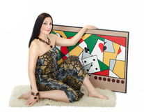 Woman artist holding with left hand her painting Obsession. Woman artist sitting on a white rug and holds with left hand her painting Obsession on white stock photography