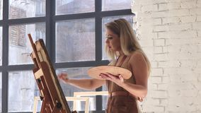 Woman artist inspired paints picture on canvas mounted on easel. In hands holds brush and palette, in background large light window and other works of master stock video footage
