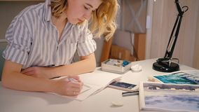 Woman artist smartphone sketching creating artwork. Woman artist looking at smartphone screen sketching. Neat workplace. Young blonde female focused creating stock video footage