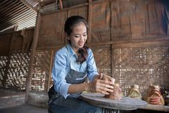 Woman artist making pottery. Asian woman making vase from fresh wet clay on pottery wheel Royalty Free Stock Images