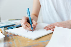 Woman artist making sketches by gel ink pen at table Stock Photography