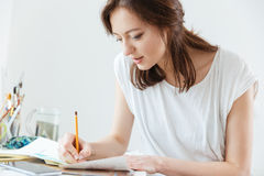 Woman artist making sketches in workshop Royalty Free Stock Image