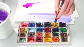 Woman artist mixing oil colours on palette holding in her hand stock footage
