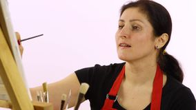 Woman artist painting with paintbrush. The woman draws a picture. The artist on a white background draws on an easel oil stock video