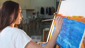 Woman artist painting a picture on easel with oil paints in her workshop.