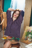 Woman artist painting a picture in loft studio. Royalty Free Stock Image