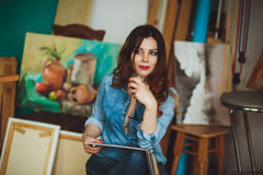 Woman artist painting a picture in a studio Royalty Free Stock Image