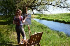 Woman artist paints landscape painting of small river. Painter rear view stock images