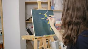 She loves painting. Woman artist with palette working on easel in the studio. She making first brush strokes with oils on canvas stock video footage