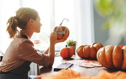 Woman artist prepares for halloween and paints pumpkins royalty free stock image