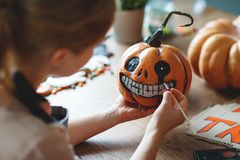 Woman artist prepares for halloween and paints pumpkins royalty free stock images