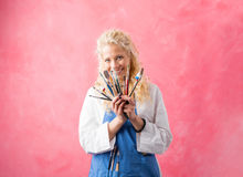Woman artist showing paint brushes Stock Images