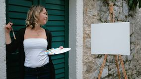 Woman artist sitting on steps of street and draws in paint pad. stock video footage