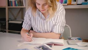 Woman artist smartphone sketching creating artwork. Woman artist looking at smartphone screen sketching. Neat workplace. Young blonde female smiling creating stock footage