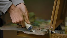 Woman artist squeezing a tube with white oil paint on a palette. Closeup detailed plan of hands of the artist girl on the background of an easel outdoor in the stock video footage