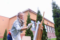 Woman artist stands with brush in hand near easel, looking and f Stock Image
