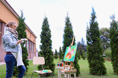 Woman artist stands with brush in hand near easel, looking and f Stock Photo