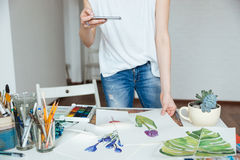 Woman artist taking photos of her drawings using smartphone. Closeup of woman artist in jeans standing and taking photos of her drawings using smartphone in royalty free stock photography