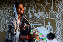 Woman Artist. A underprivileged woman artist doing folk painting in the remote village of West Bengal,India where a few families having a traditional form of Stock Image