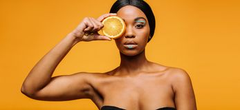 Woman with artistic make-up holding an orange Royalty Free Stock Image