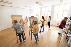 Woman artists with brushes painting at art school Stock Photography