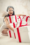 Woman as angel with heap of gift boxes indoors Stock Photo