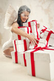 Woman as angel with heap of gift boxes indoors Royalty Free Stock Photography