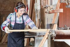 Woman as apprentice at carpentry shop Stock Image
