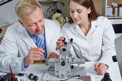 Woman as apprentice in optician. Young women as apprentice in optician workshop on drilling machine royalty free stock images