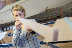 Woman as carpenter during apprenticeship lesson. Checking royalty free stock photography