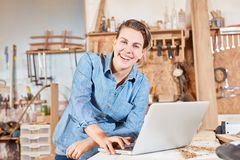 Woman as carpenter trainee at laptop computer stock images