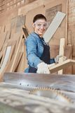 Woman as carpenter. Working on wood processing royalty free stock image