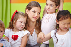 Woman as child care worker. In kindergarten with a group of children Royalty Free Stock Photography