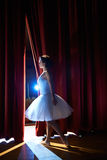 Woman as classic dancer looking at stalls before ballet. Arts and entertainment in theatre with female classic dancer in tutu, standing behind the scenes and Royalty Free Stock Images
