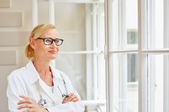 Woman as competent medical specialist. With arms crossed smiling royalty free stock photo