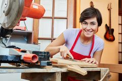 Woman as craftsman in woodworking apprenticeship. In guitar workshop royalty free stock image