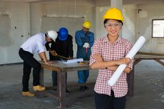 Woman as Foreman wear Yellow Hardhat holding Blueprint Standing. With construction Team worker or Colleague as Teamwork Partnership and Business collaboration Royalty Free Stock Photo
