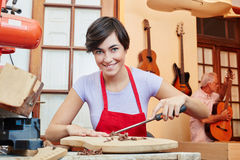 Woman as guitar maker trainee. In wood apprenticeship Stock Images