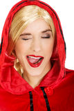 Woman as a Little Red Riding Hood blinks eye. Royalty Free Stock Photos