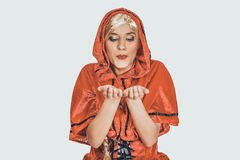 Woman as a Little Red Riding Hood blowing kiss. Royalty Free Stock Photography